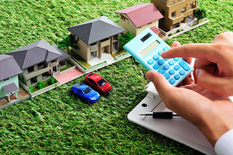 並んでいる住宅模型と予算を計算している様子
